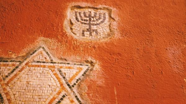 Auf einer Wand sind das Mosaik eines Davidstern und einer Menora zu sehen
