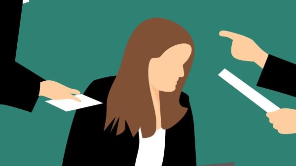 Zu sehen ist eine Illustration von einer Person mit langen hellbraunen Haaren in einer Arbeitssituation im Büro. Die Person schaut nach unten. Links und rechts am Bildrand sind Arme zu sehen, die auf die Person zeigen beziehungsweise ihr Briefe hinhalten. Es scheint eine Konfliktsituation zu sein.