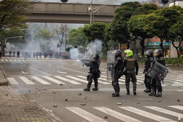 Polizei auf verlassener Straße schießen Tränengas. Im Hintergrund stehen vereinzelte Demonstrant*innen.