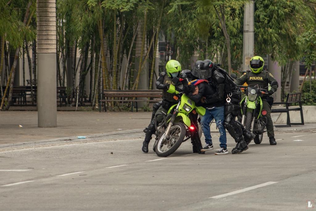3 Polizisten bedrängen und drücken Demonstranten auf leerer Straße auf ein Motorrad.