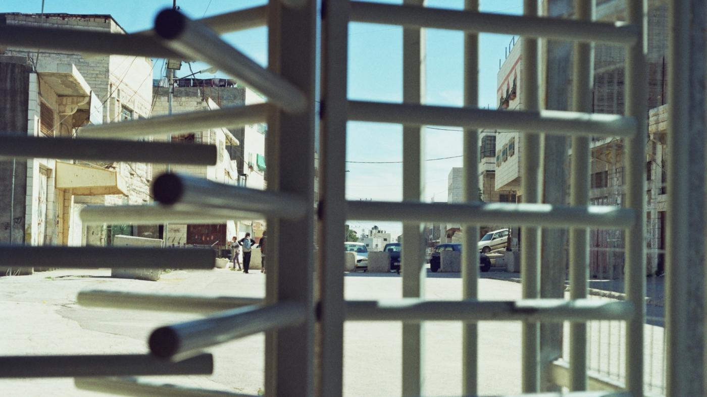 Im Vordergrund ist ein Gitter-Drehkreuz eines Checkpoints zu sehen, dahinter ein Teil der Altstadt Hebrons (Westjordanland).
