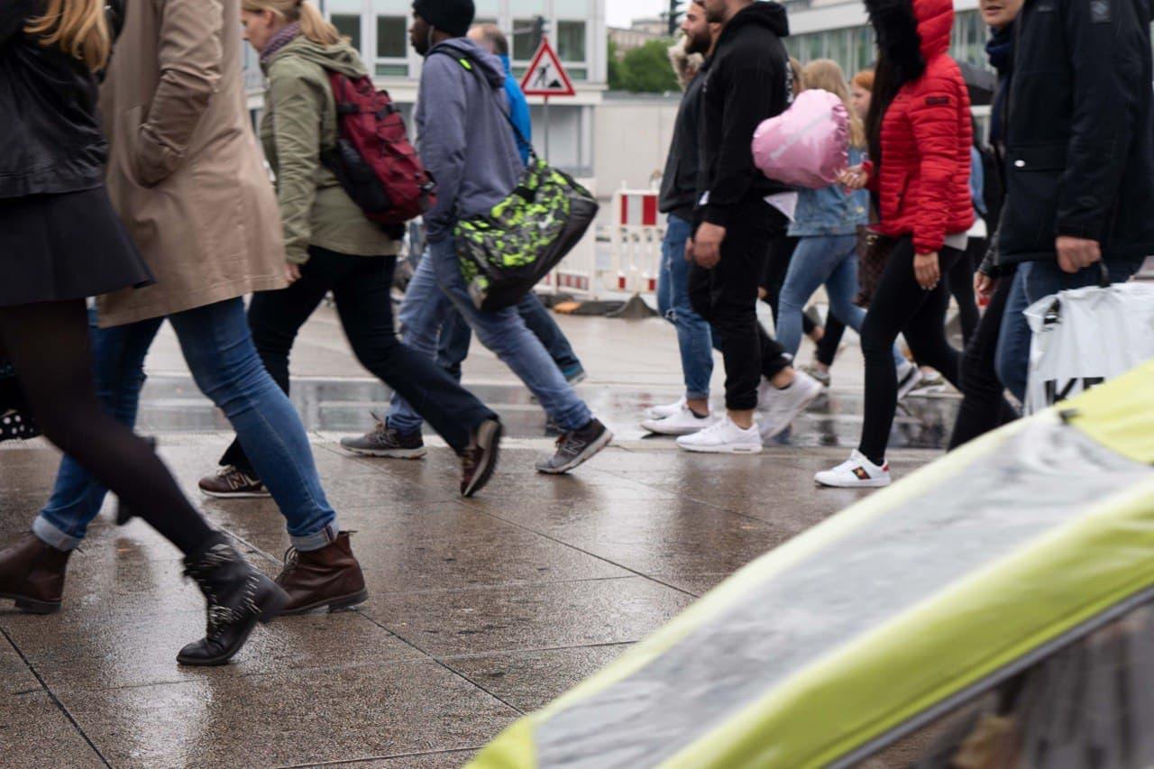 Leute laufen von rechts nach links auf nassem Asphalt
