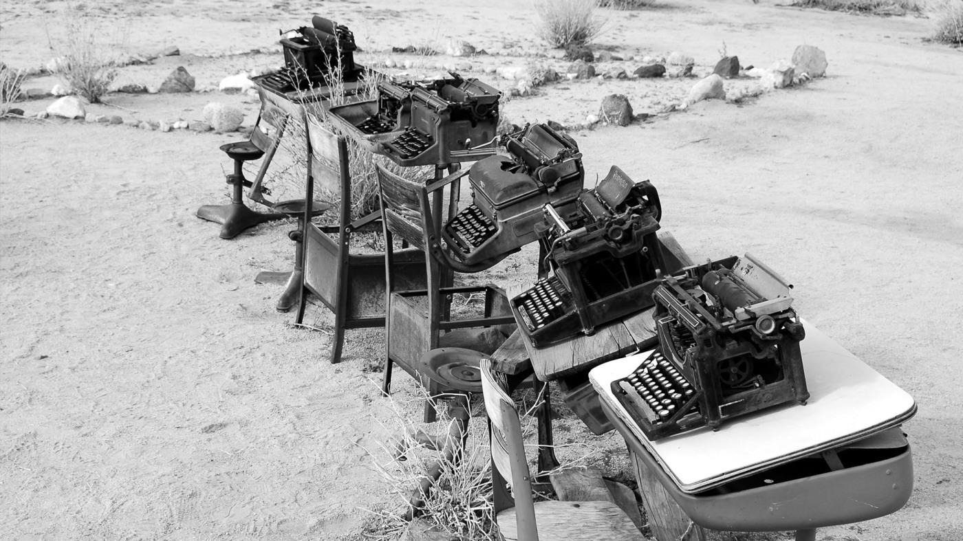 Fünf Schulbänke mit jeweils einer alten Schreibmaschine darauf in der Natur. Die Fotografie ist schwarz-weiß.